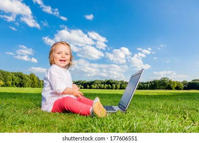 laughing child outdoor on computer