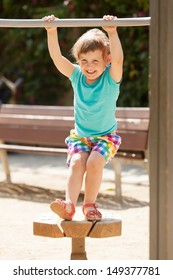 Laughing child  at playground  in sunny summer day