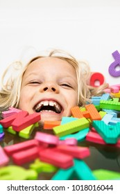 Laughing child playing with foam letters