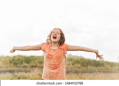 Laughing child spread its arms and catches raindrops. Freedom, happy childhood, healthy lifestyle concept.