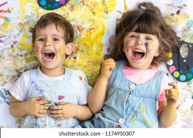 Laughing children with color paint dots on face with colors and brushes lying on floor.