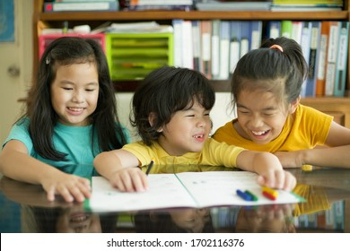 Laughing children doing homework.Cheerful girls and boy learning together.Siblings home education.Boy preschooler with sisters.Group study.Elementary and preschool students.Math lesson with workbook.