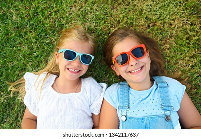 Laughing children wearing sunglasses relaxing during summer day on the green grass
