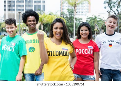 Laughing colombian sports fan with supporters from Mexico, Brazil, Germany and Russia outdoors on way to stadium