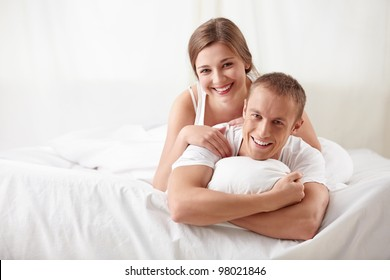 Laughing couple in bedroom