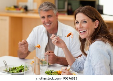 Laughing couple eating dinner together