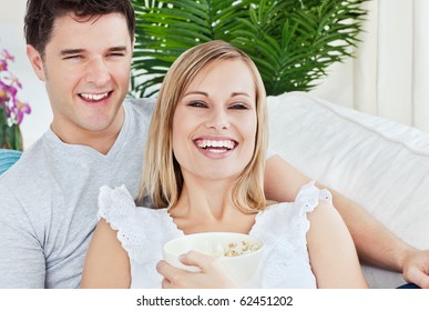 Laughing couple eating pop-corn lying on the sofa in the living-room during the day