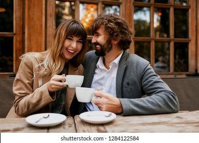 Laughing couple in love.  Handsome man with beard and his elegant wife enjoying  coffee break   in cafe outdoor.  Couple hugging and talking.