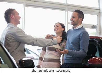 Laughing couple receiving keys from a salesman in a car shop