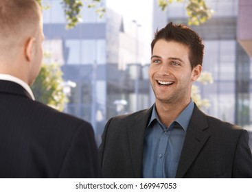 Laughing coworkers standing outside of business office, talking.