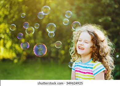 Laughing curly girl with bubbles.  Happy childhood concept.