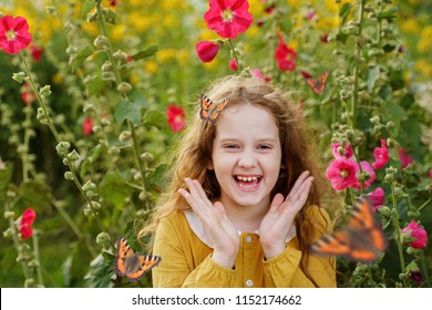 Laughing curly girl with a butterfly on her hair showing white teeth. Healthy, medical  and happy childhood concept.