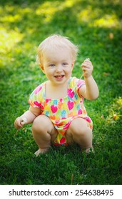 Laughing cute adorable blond baby toddler sitting on a meadow green grass during summer day holding flower dandelion