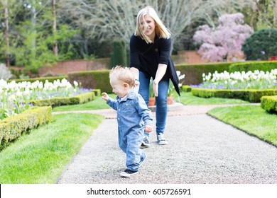 laughing cute toddler boy running away from young mother making first steps enjoying time together in the park