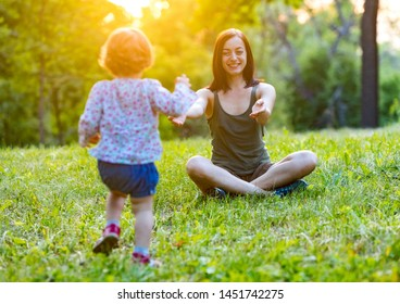 Laughing cute toddler girl running away from young mother making first steps enjoying time together in the park