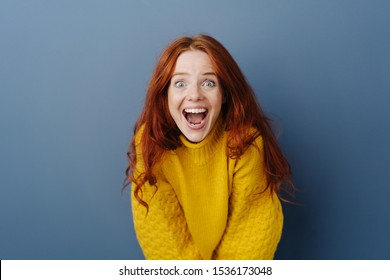 Laughing delighted young woman leaning forwards towards the camera with a look of amazement and awe over a blue studio background with copy space