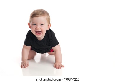 A laughing, eight month old, baby boy crawling toward the camera on a white, seamless background.