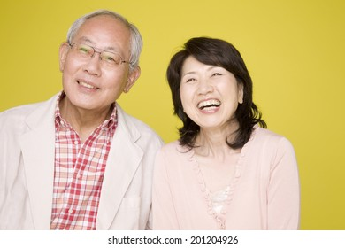 The laughing elderly couple by their bodies snuggled