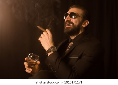 The laughing elegant man or mafia boss in suit is smoking cigar and holding alcohol in hand, sepia photo, retro style.