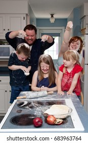 laughing Family food fight with flour in the kitchen.
