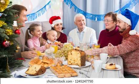 Laughing family members making conversation during Christmas dinner