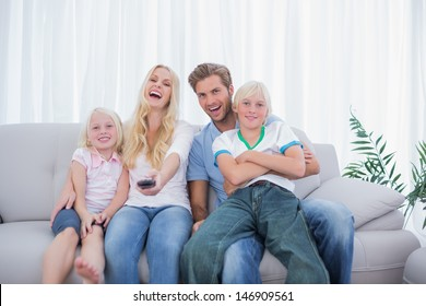 Laughing family watching TV together in the living room