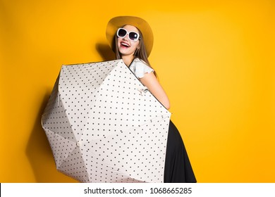 laughing fashionable model girl in sunglasses and hat posing with big umbrella