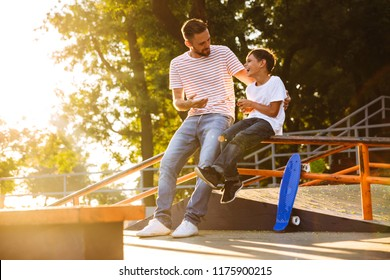 Laughing father spending time with his little son at the skate park, hugging