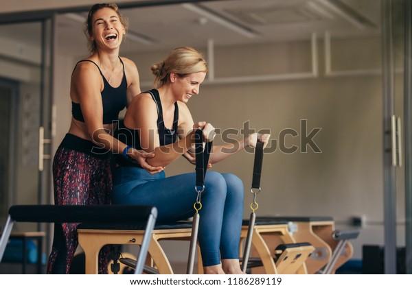 Rindo trainer fêmea ajudando uma mulher em puxar bandas esticadas sentado na máquina de treinamento pilates. Mulher sorridente na academia fazendo treinamento de pilates com seu treinador.