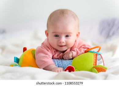 Laughing five months old infant Baby girl on a bed on her belly looking down. With a colorful toy.