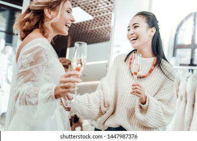 Laughing with a friend. Beautiful bridesmaid cheering up her friend bride drinking champagne together.
