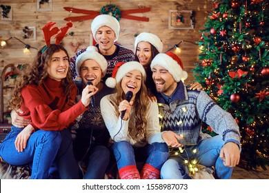 Laughing friends celebrating Christmas in karaoke