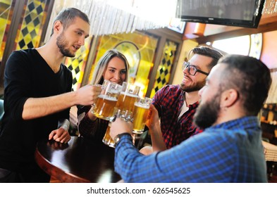 Laughing friends communicate and drink beer in a cafe or a pub