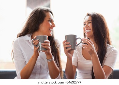 Laughing friends having a coffee in a cafe