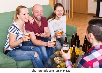 Laughing friends having fun at house party together