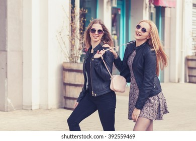 Laughing friends on the street in fashion clothes outside shooting. Happines and smiling