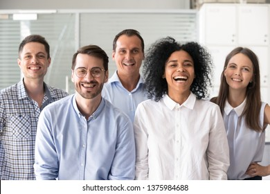 Laughing funny diverse office workers group, multiracial employees looking at camera, motivated successful business people, staff posing together in modern office, multi-ethnic colleagues portrait