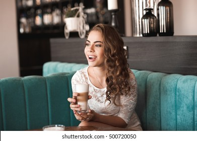 Laughing girl 20-24 year old sitting in cafe drinking coffee/ Wearing stylish white dress.