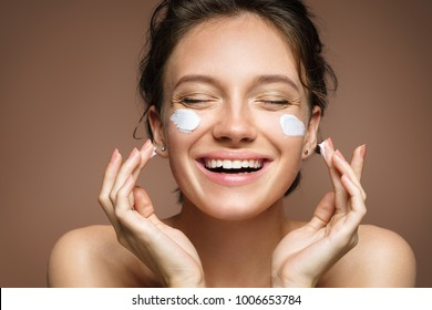 Laughing girl applying moisturizing cream on her face. Photo of young girl with flawless skin on brown background. Skin care and beauty concept