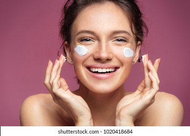Laughing girl applying moisturizing cream on her face. Photo of young girl with flawless skin on pink background. Skin care and beauty concept