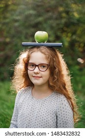 Laughing girl with a book and apple on his head. Easy learning concept.