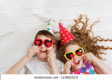Laughing girl and boy with sunglasses, hold candles heart form, lying on the wooden floor. Christmas, New Year or Valentines day concept.