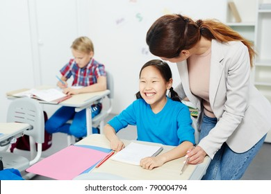 Laughing girl by desk looking at blackboard while listening to her teacher near by