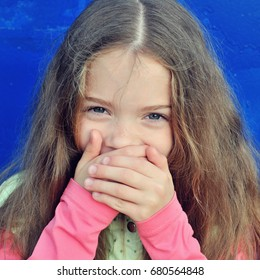 Laughing girl covers her mouth with her hands