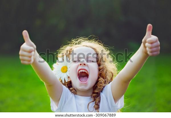 Lachen Mädchen mit Gänseblümchen in ihren Haaren, zeigen Daumen auf.