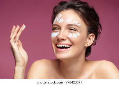 Laughing girl with flawless skin applying moisturizer cream on her face on pink background. Facial treatment