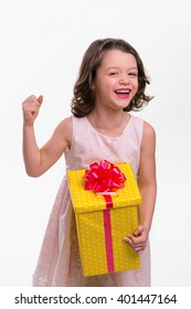 Laughing girl with a gift for her birthday. Nice idea of a present for a little sister or daughter. True and sincere emotions of joy.