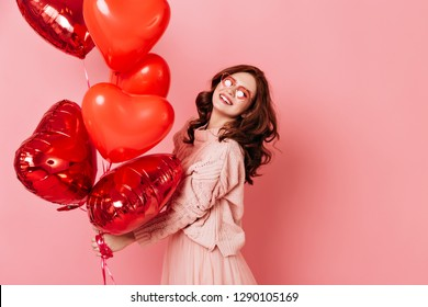 Laughing girl holding bunch of heart shaped party balloons. Studio portrait of wonderful ginger lady isolated on pink.