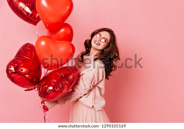 ハート型のパーティー風船束を持つ笑う女の子。ピンクの背景にスタジオでの生姜の女性のポートレート。