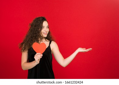 Laughing girl holding valentine heart and pointing with hand isolated on red background.